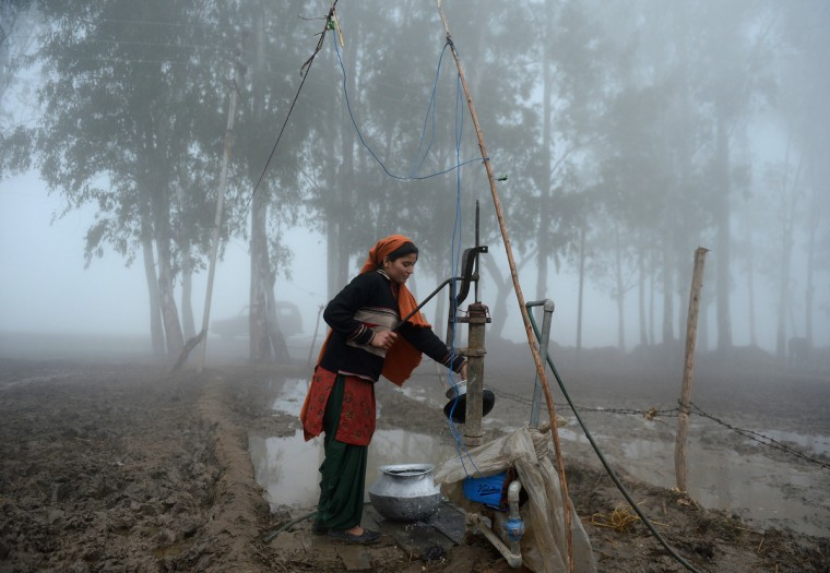 An Indian woman uses a handpump to during a dense fog along the India-Pakistan border in Suchit-Garh, 36 kms southwest of Jammu. The beheading of an Indian soldier may have sparked a war of words between Delhi and Islamabad but the two nuclear rivals are both determined to prevent it from wrecking a fragile peace process. (Tauseef Mustafa/Getty Images)