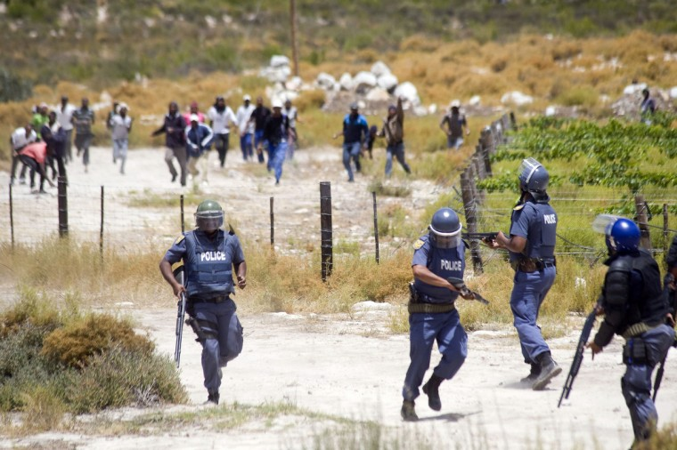 Members of the South African Police Services retreat from a group of rock-throwing striking farmworkers during violent clashes in de Doorns, a small farming town about 140Km North of Cape Town, South Africa. The farm workers have said that they they will not return to work on the fruit growing region's farms until they receive a daily wage of at least R150($17) per day, which is about double what they currently earn. (Rodger Bosch/Getty Images)