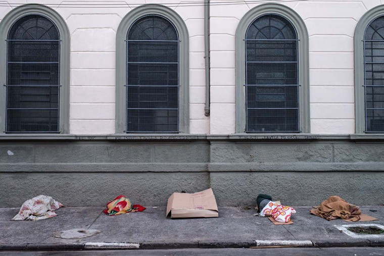 "Drug addicts sleep along the sidewalk next to a CathoLic church at so called ""Crackolandia"", a place where drug users gathering to smoke crack cocaine, in downtown Sao Paulo, Brazil on January 11, 2013.(Yasuyoshi Chiba/AFP/Getty Images)"