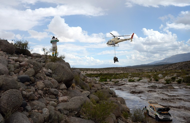 Brazil's Guilherme Spinelli (L) observes his Mitsubishi stuck in a river below next to co-driver Youssef Haddad, as a helicopter passes with an unidentified bike, during Stage 8 of the Dakar Rally 2013 between Salta and Tucuman, Argentina, on January 12, 2013. The rally takes place in Peru, Argentina and Chile from January 5-20. (Franck Fife/Getty Images)