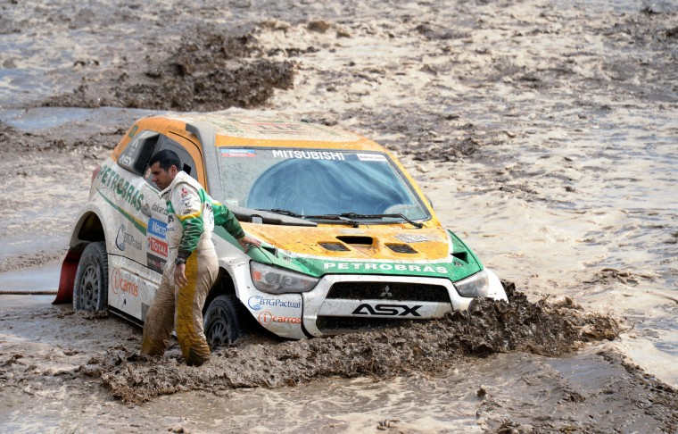 Brazil's Youssef Haddad stands next to his Mitsubishi stuck in a river during Stage 8 of the Dakar Rally 2013 between Salta and Tucuman, Argentina, on January 12, 2013. The rally takes place in Peru, Argentina and Chile from January 5-20. (Franck Fife/Getty Images)