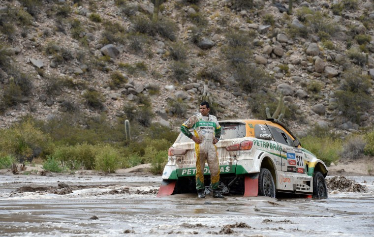 Brazil's Youssef Haddad stands next to his Mitsubishi stuck in a river during Stage 8 of the Dakar Rally 2013 between Salta and Tucuman, Argentina, on January 12, 2013. (Franck Fife/Getty Images)