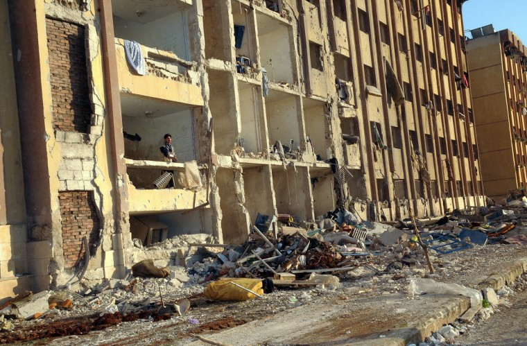 A Syrian man stands in the debris following an explosion outside Aleppo University, between the university dormitories and the architecture faculty, on January 15, 2013. Fifteen people were killed and dozens of others injured in a blast that rocked Aleppo University, the top academic institution in northern Syria's embattled city, said a monitoring group. (Getty Images)
