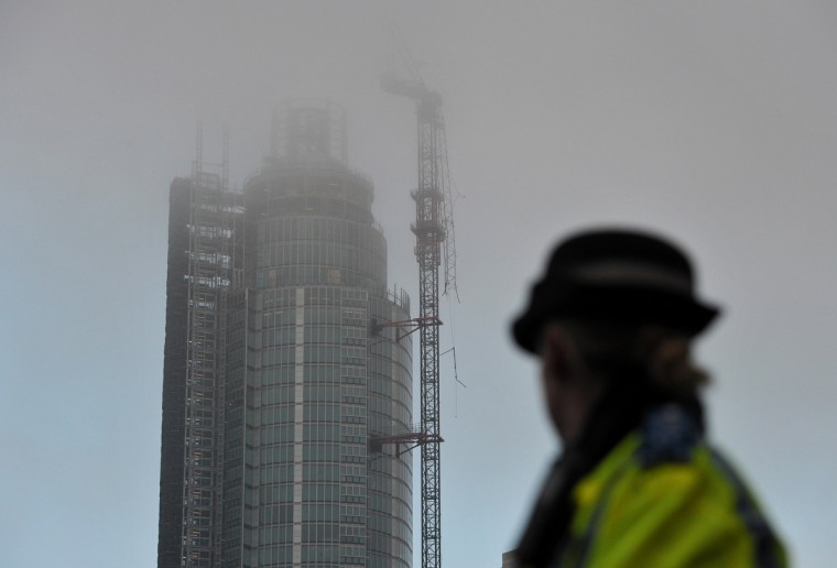 A policewoman looks at a damaged crane that was hit by a helicopter following the crash in central London. Two people were killed after a helicopter hit a crane at a building site and plunged to the ground in a ball of flames, police said. (Carl Court/Getty Images)