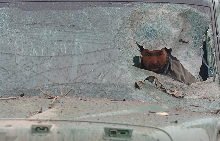 An Afghan truck driver is seen through the broken windshield of his vehicle at the site of a suicide attack near the Afghan intelligence agency headquarters in Kabul. A squad of suicide bombers attacked the national intelligence agency headquarters in heavily-fortified central Kabul on January 16, killing at least two guards and wounding dozens of civilians, officials said. (Shah Marai/Getty Images)