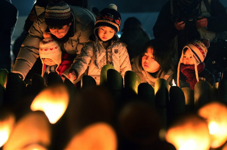 "People light candles and pray during a memorial service for the victims of the 1995 ""Great Hanshin earthquake"", at a park in Kobe, Hyogo prefecture in western Japan. Memorial services were held to mark the 18th anniversary of the 1995 massive earthquake, which stuck just before dawn and killed more than 6,400 people. (Jiji Press/Getty Images)"
