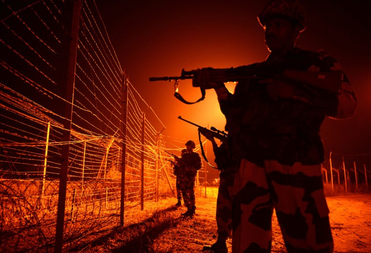 An Indian Border Security Force (BSF) soldier patrols along the border fence at an outpost along the India-Pakistan border in Abdulian, 38 kms southwest of Jammu. A ceasefire took hold January 17 in disputed Kashmir after the Indian and Pakistani armies agreed to halt deadly cross-border firing that had threatened to unravel a fragile peace process. (Tauseef Mustafa/Getty Images)