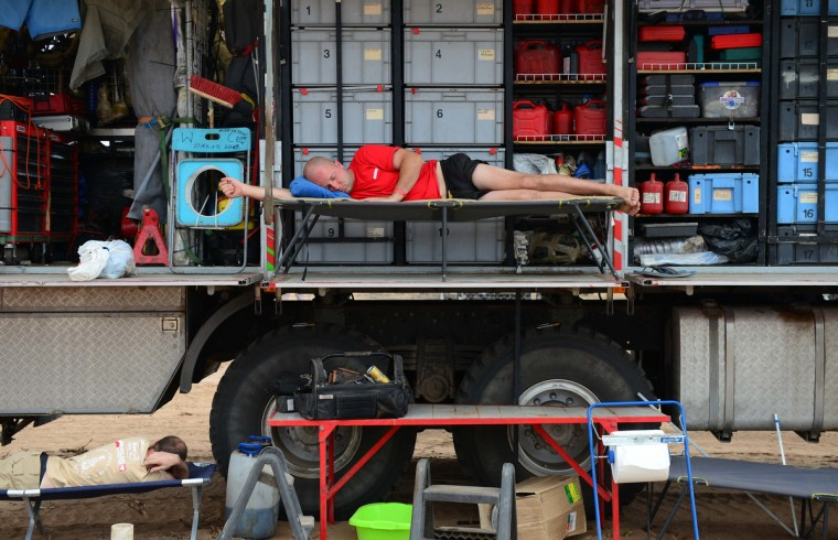 A mechanic rests on a truck during Stage 13 of the 2013 Dakar Rally between Copiapo and La Serena, in Chile, on January 18, 2013. The rally is taking place in Peru, Argentina and Chile from January 5 to 20. (Franck Fife/Getty Images)