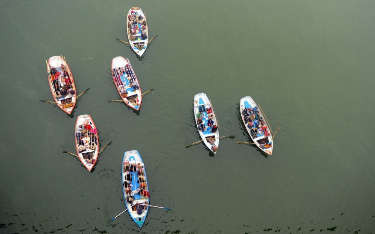 Indian Hindu pilgrims travel on boats to take a holy dip at Sangam, the confluence of the Rivers Ganges, Yamuna and the mythical Saraswati during the Maha Kumbh Mela in Allahabad. The Kumbh Mela in the Indian town of Allahabad will see up to 100 million worshippers gather over the next 55 days to take a ritual bath in the holy waters, believed to cleanse sins and bestow blessings. (Sanjay Kanojia/Getty Images)