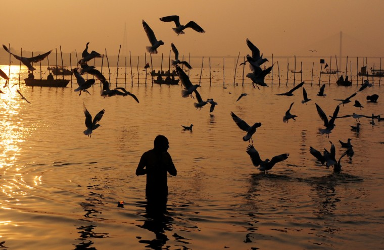An Indian Hindu devotee takes a dip in the Sangam, the confluence of the rivers Ganges and Yamuna in Allahabad. The Kumbh Mela in the Indian town of Allahabad will see up to 100 million worshippers gather over the next 55 days to take a ritual bath in the holy waters, believed to cleanse sins and bestow blessings. (Sanjay Kanojia/Getty Images)