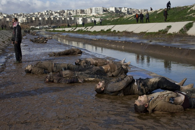 A Syrian man stands next to the bodies of executed men on the side of a canal in the northern Syrian city of Aleppo on January 29, 2013. The bodies of at least 68 unidentified young men and boys, all executed with a single gunshot to the head or neck, were found in the Quweiq River, which separates the Bustan al-Qasr district from Ansari in the southwest of Aleppo, in a rebel-held area where a Free Syrian Army captain said many more were still being dragged from the water. (JM Lopez/Getty Images)