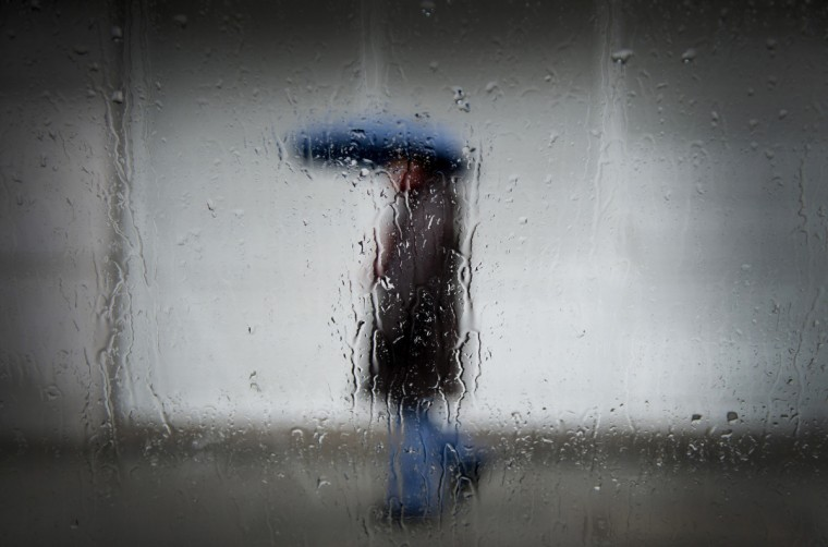 A man shelters from the rain under an umbrella in Munich, southern Germany. Raising temperatures brought rain to many parts of the country. (Andreas Gebert/Getty Images)