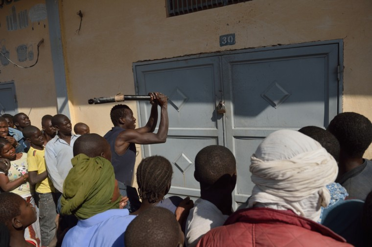 "A Malian tries to break the lock off a store front as looters and residents stand by in the streets of Timbuktu. Hundreds of Malians looted stores in Timbuktu on Tuesday, saying the shops belonged to ""Arabs"" and ""terrorists"" linked to the radical Islamists who occupied the desert town for 10 months. (Eric Feferberg/Getty Images)"