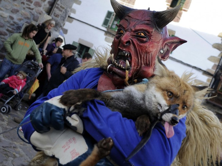 A masked man holds a fox during the carnival of Zubieta, in the northern Spanish province of Navarra province. (Rafa Rivas/Getty Images)