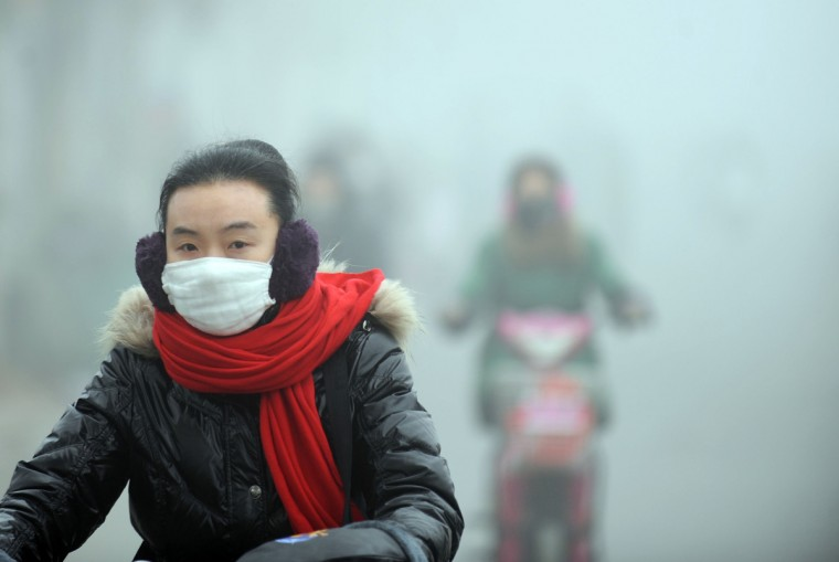 "A woman rides a bike in the heavy smog with a mask on a street in Haozhou, central China's Anhui province. Across China public frustration mounted this week as dense smog blanketed swathes of the country, with even state-run media questioning the authorities' ability to meet their goal of building a ""beautiful China"". (Getty Images)"