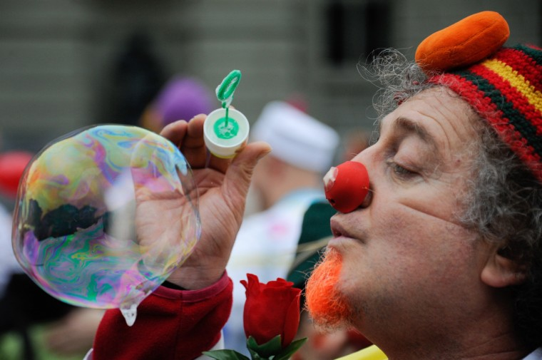 "One of the clows blows bubbles as around 2OO ""Clown Doctors"" or ""Giggle Doctors"" of the children care foundation Theodora gather on January 30, 2013 on the Federal Place during a trip to Bern, Switzerland. Hospital clowns from around the world are on a week course in Rolle, western Switzerland. The Theodora foundation was created in 1993 with the goal of relieving the suffering of hospitalized children through regular visits by professional artists called the ""Clown/Giggle Doctors"". AFP PHOTO / SEBASTIEN BOZONSEBASTIEN BOZON/AFP/Getty Images ORG XMIT:"