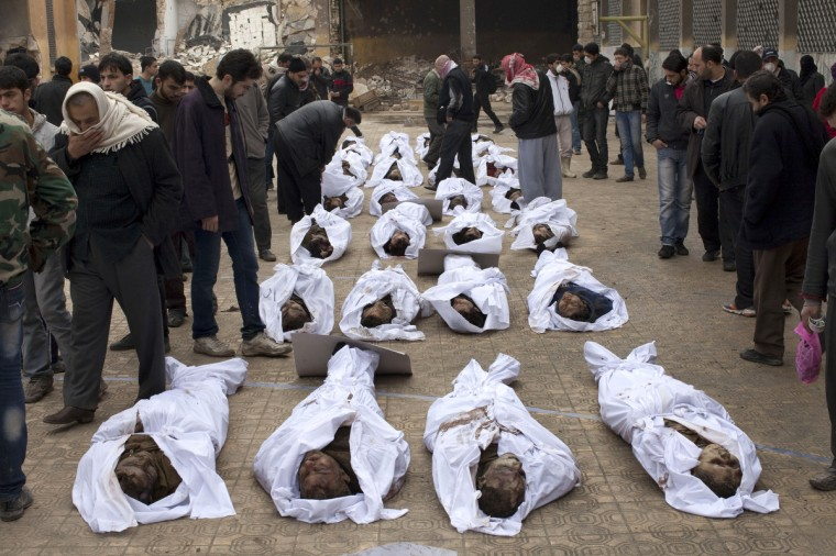 """Men search for their relatives amongst the bodies of Syrian civilians executed and dumped in the Quweiq river, in the grounds of the courtyard of the Yarmouk School, in the Bustan al-Qasr district of Aleppo on January 30, 2013. Syria's opposition charged that """"global inaction"""" was giving Bashar al-Assad's regime a license to kill, a day after dozens of young men were found shot execution-style in the city of Aleppo. (JM Lopez/Getty Images)"""