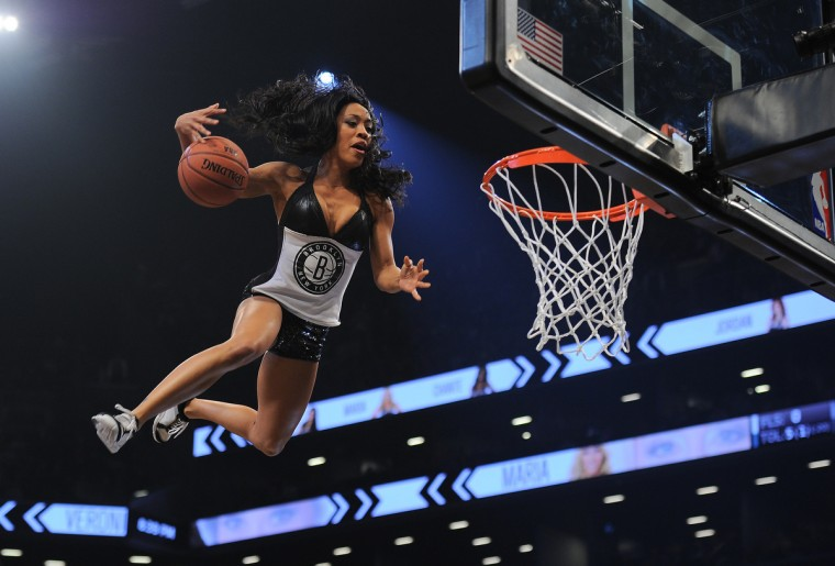 A Brooklyn Nets cheerleader slam dunks a ball during a break while entertaining the crowd during the Nets's game against the Miami Heat during their NBA game at the Barclays Center in the Brooklyn borough of New York City. (Emmanuel Dunand/Getty Images)