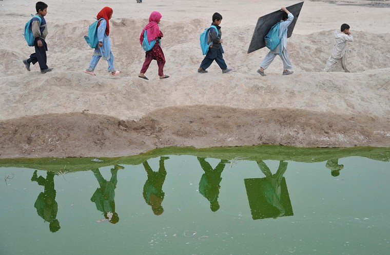 Afghan school children walk home after classes near an open classroom in the outskirts of Jalalabad. Afghanistan has had only rare moments of peace over the past 30 years, its education system being undermined by the Soviet invasion of 1979, a civil war in the 1990s and five years of Taliban rule. (Noorullah Shirzada/Getty Images)