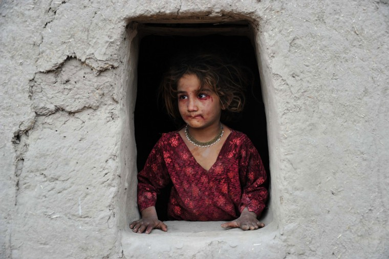An Afghan girl looks out of her window near an open classroom on the outskirts of Jalalabad. Afghanistan has had only rare moments of peace over the past 30 years, its education system being undermined by the Soviet invasion of 1979, a civil war in the 1990s and five years of Taliban rule. (Noorullah Shirzada/Getty Images)