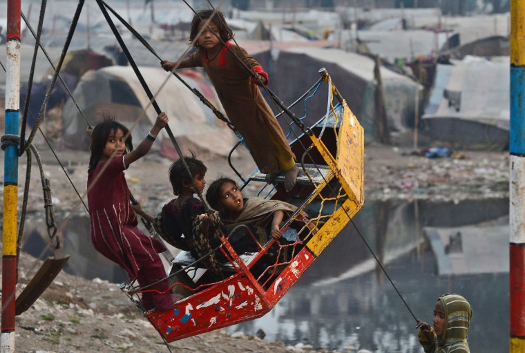 Pakistani gypsy children enjoy playing on a swing near their makeshift tents in Lahore. Year-on-year inflation stood at 6.9 percent in November, the State Bank of Pakistan said in a statement, a faster fall than had been estimated. Food inflation dropped to 5.3 percent and non-food inflation to 8.1 percent. (Arif Ali/Getty Images)