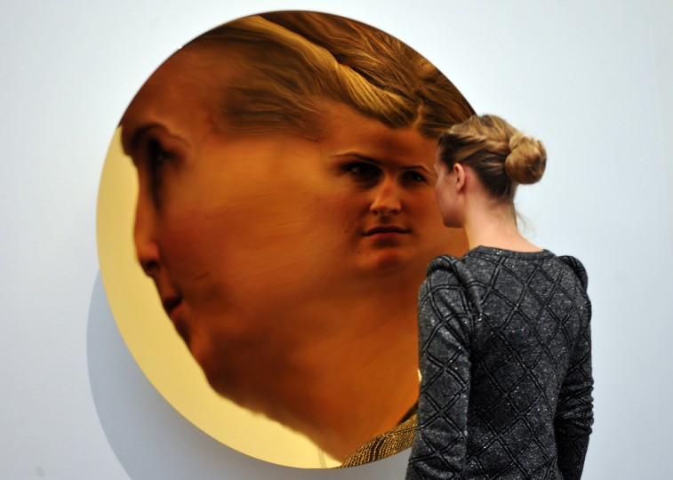 A member of staff poses next to a work entitled 'Untitled' by British artist Anish Kapoor in which her face is reflected at Sotheby's auction house in central London. Due to form part of the Contemporary Art Evening Sale on February 12, it is expected to fetch between 450,000-650,000 GBP (560,000-810,000 EUR - 725,000-1,050,000 USD). (Carl Court/Getty Images)