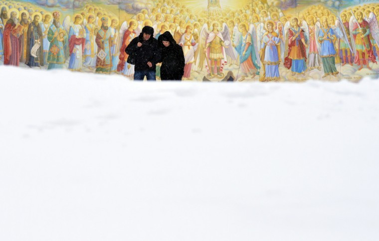 A couple walks during heavy snow fall in front of frescos of Mykhaylo Gold Domes Cathedral in the center of the Ukrainian capital of Kiev. (Sergei Supinsky/Getty Images)