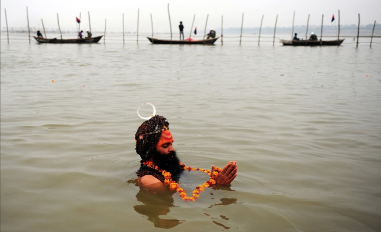 An Indian sadhu - holy man - takes a 'holy dip' at the 'Sangam', the confluence of the rivers Ganges, Yamuna and mythical Saraswati during the Maha Kumbh festival in Allahabad. The Kumbh Mela in the town of Allahabad will see up to 100 million worshippers gather over 55 days to take a ritual bath in the holy waters, believed to cleanse sins and bestow blessings. (Sanjay Kanojia/Getty Images)