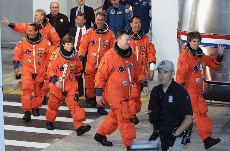 Space Shuttle Discovery astronauts Charles Camarda, Andrew Thomas, Wendy Lawrence, Stephen Robinson, pilot Jim Kelly, Soichi Noguchi, of JAXA, and commander Eileen Collins (L to R) leave the crew quarters to load into the astronaut van and be driven to launch complex 39-B at Kennedy Space Center July 26, 2005, in Cape Canaveral, Florida. Discovery is scheduled for launch July 26 and will be the first shuttle launched since the Columbia disaster over two years ago. (Mark Wilson/Getty Images)