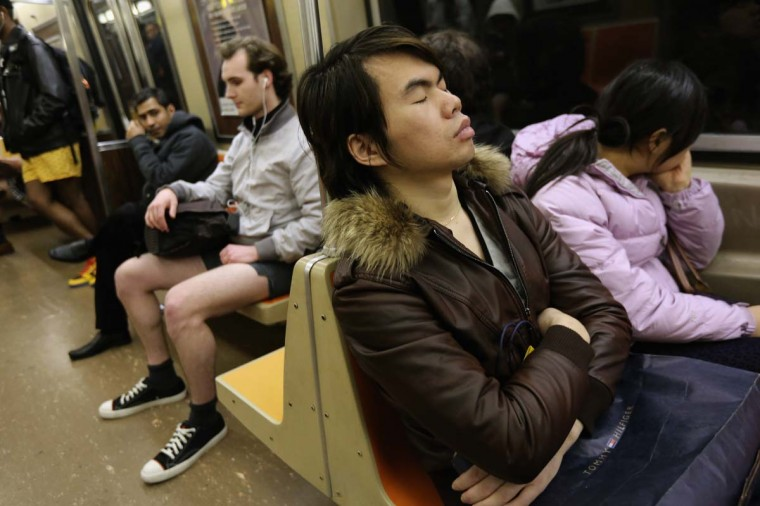 "One subway passenger sleeps as others ride the train pantless on January 13, 2013 in New York City. Thousands of people participated in the 12th annual No Pants Subway Ride, organized by New York City prank collective Improv Everywhere. During the afternoon winter event, participants boarded separate subway stops and removed their pants, pretending that they did not know each other. The event, refered to as a ""celebration of silliness"" is designed to make fellow subway riders laugh and smile. (John Moore/Getty Images)"