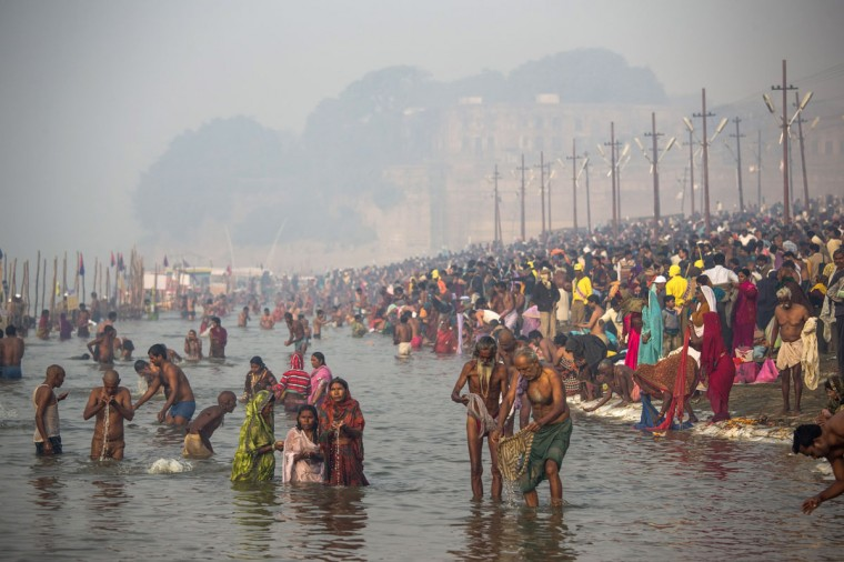 Hindu devotees bathe in the waters of Sangam, the confluence of the holy rivers Ganges, Yamuna and the mythical Saraswati, during the Maha Kumbh Mela in Allahabad, India. The Maha Kumbh Mela, believed to be the largest religious gathering on earth is held every 12 years on the banks of Sangam, the confluence of the holy rivers Ganga, Yamuna and the mythical Saraswati. (Daniel Berehulak/Getty Images)