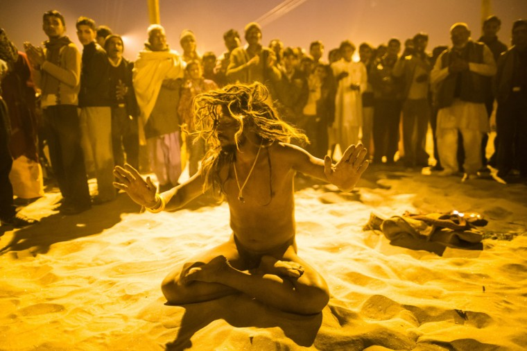 A naga sadhu performs during an aarti ceremony on the banks of the Ganges river during the Maha Kumbh Mela in Allahabad, India. The Kumbh Mela alternates between the cities of Nasik, Allahabad, Ujjain and Haridwar every three years. The Maha Kumbh Mela celebrated at the holy site of Sangam in Allahabad, is the largest and holiest, celebrated over 55 days, it is expected to attract over 100 million people. (Daniel Berehulak/Getty Images)