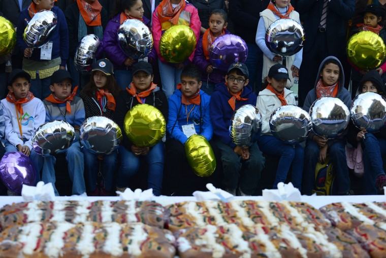 "Children wait to get a piece of the traditional ""Rosca de Reyes"" (kings' ring), a large ring-shaped bread roll baked for Epiphany, in Mexico City, on January 3, 2013. Weighing 10 metric tons (about 22,000 pounds) and measuring 1900 meters around, this 'rosca de reyes' was the world's biggest and was distributed among 200,000 people at Zocalo Square in the Mexican capital. (Alfredo Estrella/AFP/Getty Images)"