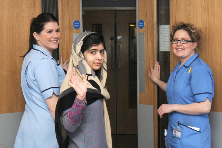 15 year-old Pakistani schoolgirl Malala Yousafzai (C) waving flanked by two members of the hospital staff as she is discharged from the Queen Elizabeth Hospital in Birmingham in central England. Malala, shot by the Taliban for campaigning for girls' education, has been discharged from the British hospital treating her. Queen Elizabeth Hospital in Birmingham, central England, said 15-year-old Malala Yousafzai would continue her rehabilitation at her family's temporary English home before undergoing major reconstructive surgery in a few weeks. (Queen Elizabeth Hospital/AFP/Getty Images)