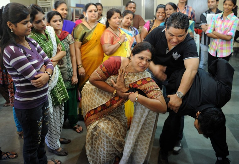 An Indian participant (C) practises a self-defence technique with an instructor during a self-defence class at a school in Mumbai. After nearly three weeks of lurid reporting on a horrifying gang-rape in New Delhi, women in the Indian capital say they are more anxious than ever, leading to a surge in interest in self-defence classes. (Punit Paranjpe/AFP/Getty Images)