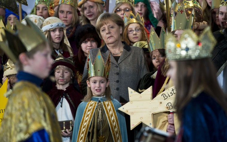 "German Chancellor Angela Merkel, center, watches as young carol singers dressed like the Magi perform a short skit at the Chancellery in Berlin on January 4, 2013. Carol singers visited the Chancellery as part of the ""Three King's Action"" charity, which focused on healthcare in Tanzania this year. (John MacDougall/AFP/Getty Images)"