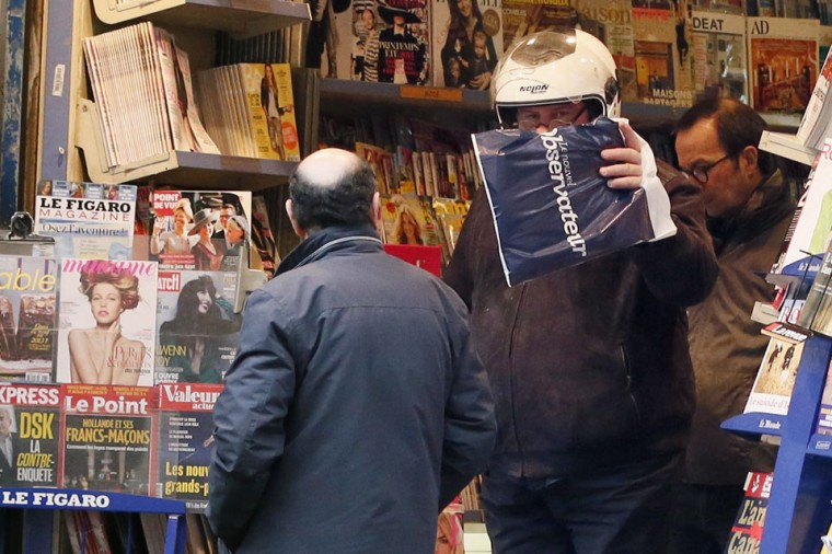 French actor Gerard Depardieu (C) hides his face as he leaves a bookshop in Paris. Russians reacted today with amusement, disbelief and a heavy dose of irony to the news that the Kremlin has granted citizenship to French actor Gerard Depardieu to solve his tax woes. (Kenzo Tribouillard/AFP/Getty Images)