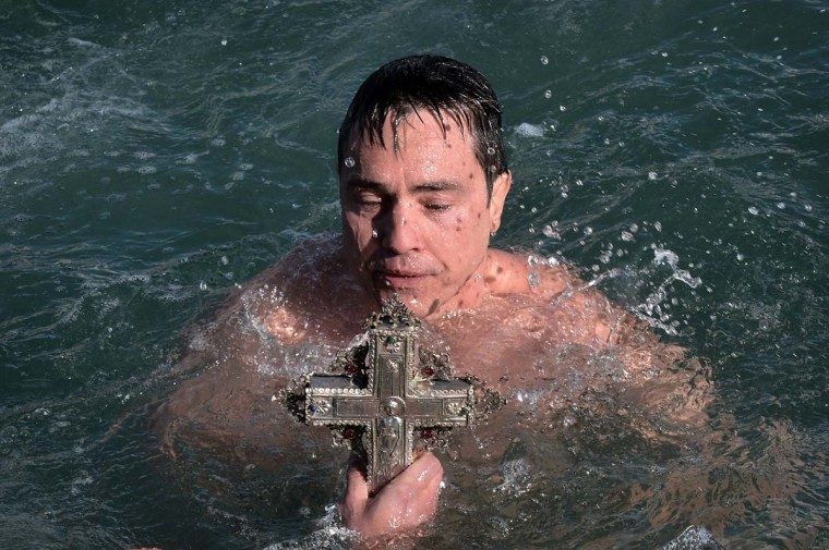A faithful holds a cross after retrieving it from the sea during the blessing of the waters marking the Epiphany Day in the city of Volos, in central Greece's region on January 6, 2013. (Louisa Gouliamaki/AFP/Getty Images)