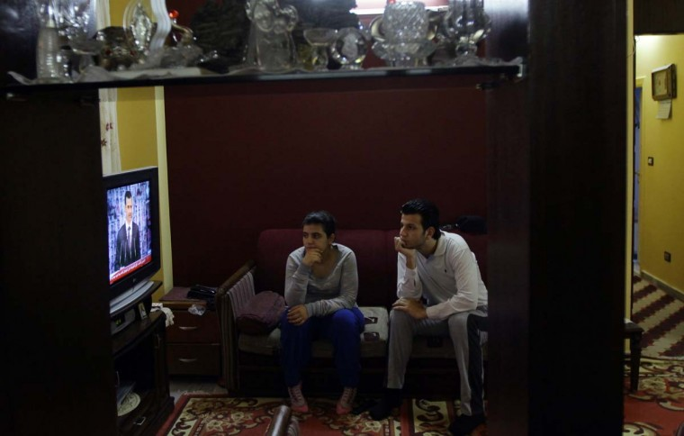 "Syrian people watch Syria's embattled President Bashar al-Assad making a public address on the state-run Syrian TV, on January 6, 2013 in Damascus. Bashar al-Assad in a rare speech Sunday denounced the opposition as ""slaves"" of the West and called for a national dialogue conference to be followed by a referendum on a national charter and parliamentary elections. (Louai Beshara/AFP/Getty Images)"