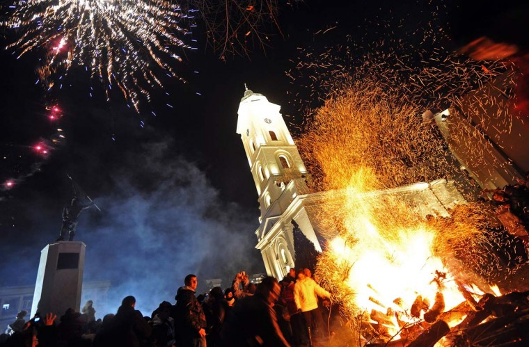 People attend a ceremonial burning of dried oak branches, the Yule log symbol for the Orthodox Christmas Eve in front of a church in Sabac, Serbia on January 6, 2013. The Orthodox faith uses the old Julian calendar in which Christmas falls 13 days after its more widespread Gregorian calendar counterpart on December 25. (Andre J. Isakovic/AFP/Getty Images)