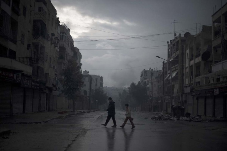 """A father and son return home with vegetables, as smoke from a pro-government forces artillery strike ascends in the background, in the al-Amaria neighbourhoodin the city of Aleppo, on January 6, 2013. Syria's embattled President Bashar al-Assad in a rare televised speech denounced the opposition as """"slaves"""" of the West and called for a national dialogue conference to be followed by a referendum on a national charter and parliamentary elections. (Stringer/Getty Images)"""