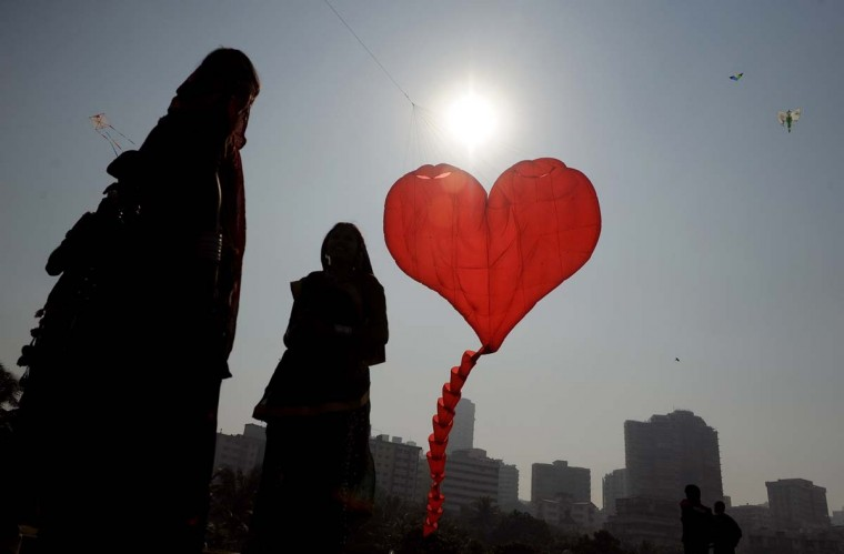 Indian visitors watch a heart-shaped kite fly during the International Kite festival on the lawns of Priyadarshani park in Mumbai on January 7, 2013. Kite enthusiasts from different countries are participating in the day-long festival. (Punit Paranjpe/AFP/Getty Images)