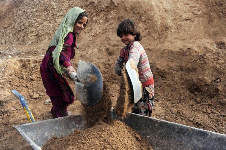 Afghan internal refugee children work at a traditional brick factory on the outskirts of Herat on January 7, 2013. In 2012 alone, spreading conflict in Afghanistan has forced more than 166,000 Afghans to flee their homes, bringing the total number of people internally displaced by conflict to at least 460,000 since the fall of the Taliban in late 2001 with conditions for the displaced falling well below international standards, according to a 2012 study by the Norwegian Refugee council. (Aref Karimi/AFP/Getty Images)