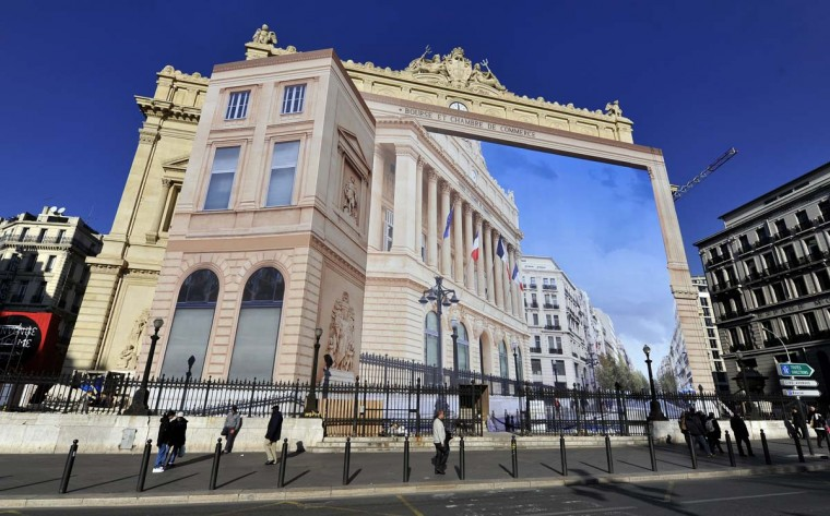 "People walk past a giant trompe-l'oeil by artist Pierre Delavie set up on the facade of the Palais de la Bourse building in Marseille, southern France, on January 7, 2013, as part of ""Marseille-Provence European Capital of Culture"" in 2013. (Gerard Julien/AFP/Getty Images)"