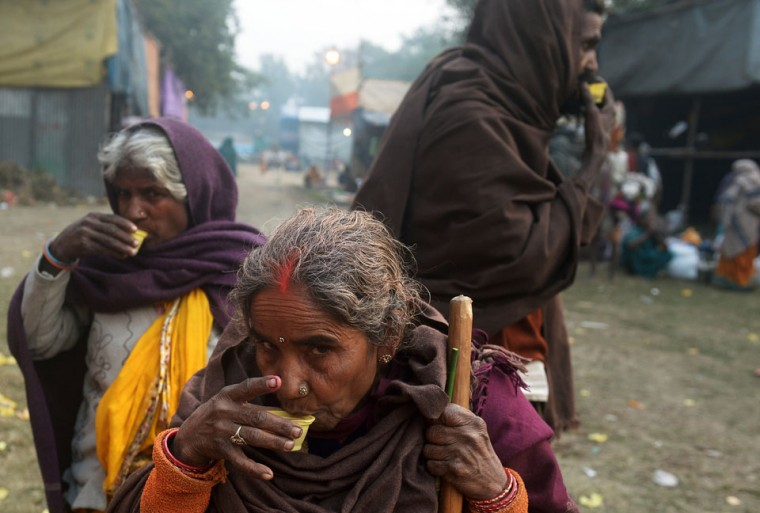 Indian villagers drink tea as they arrive at temporary camp in Kolkata, while making their way to The Gangasagar Mela. As thousands of homeless people sought places in temporary shelters, the unusual cold in throughout India has been attributed to dense fog which has obscured the sun and disrupted airports and trains, as well as icy winds from the snowy Himalayas to the north. (Dibyangshu Sarkar/AFP/Getty Images)