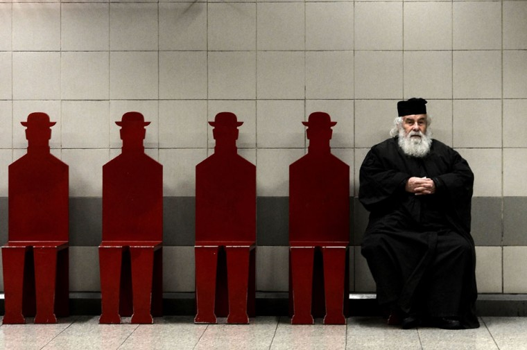 A Greek Orthodox priest sits on a bench in an Athens metro station. (Aris Messinis/AFP/Getty Images)