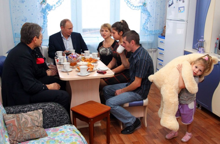 Russian President Vladimir Putin (C) speaks with the Zagursky family in their new flat during a visit to the town of Krymsk in the southern Russian Krasnodar region. The country's worst flooding disaster of recent history killed at least 171 people while nearly 35,000 people lost part or all of their belongings in the flooding on July 7, 2012. (Mikhail Klimentyev/AFP/Getty Images)