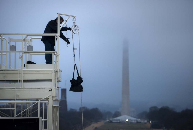 A worker uses a pulley to bring a bag to the top of a camera tower before an inauguration rehearsal on Capitol Hill January 13, 2013 in Washington, DC. President Barack Obama and Vice President Joe Biden will be ceremonially sworn in for a second four-year term during the 57th Inauguration on January 21. (Brendan Smialowski/AFP/Getty Images)