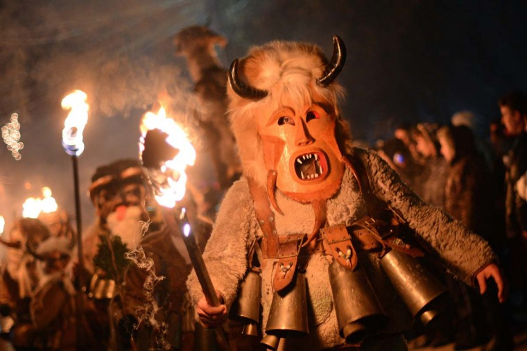 "Bulgarian dancers named ""Kukeri"" hold torches as they perform a ritual dance during the Kukeri Carnival in the village of Batanovci, western Bulgaria, on January 13, 2013. The Kukeri Carnival is a festival of brightly colored masks and costumes which marks the beginning of the spring. Every participant makes his own multi-colored personal mask, covered with beads, ribbons and woolen tassels. The heavy swaying of the main mummer is meant to represent wheat heavy with grain, and the bells tied around the waist are intended to drive away the evil spirits and the sickness. (Dimitar Dilkoff/AFP/Getty Images)"