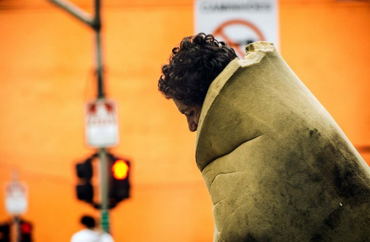 "A homeless wrapped up in a matress walks in""Crackolandia"", a place where addicts gather to smoke crack, in downtown Sao Paulo Brazil on January 14, 2013. (Yasuyoshi Chiba/AFP/Getty Images)"